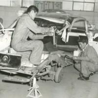 Boys work on a seriously damaged car in an auto mechanics class.